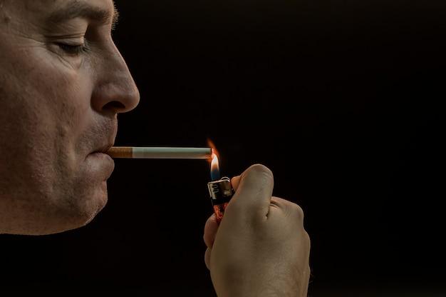L'homme fume la cigarette sur fond noir. homme mystère avec cigare et fumée isolé sur fond noir. tage sombre et maussade d'un jeune homme fumant sur un fond noir