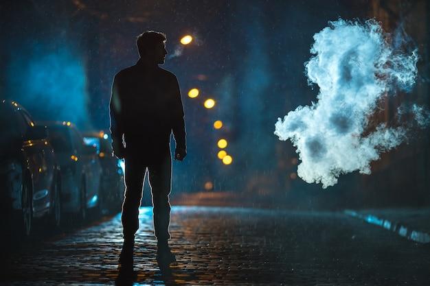 L'homme fume dans le nuage de fumée. le soir la nuit. prise de vue au téléobjectif
