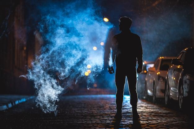 L'homme fume dans la rue. le soir la nuit. prise de vue au téléobjectif