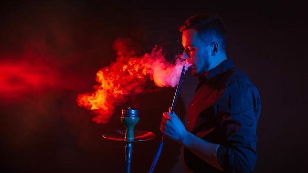 L'homme fume un narguilé dans un bar et souffle un nuage de fumée