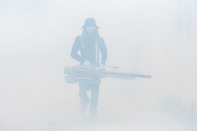 Un homme fumigation chimique pour éliminer les moustiques