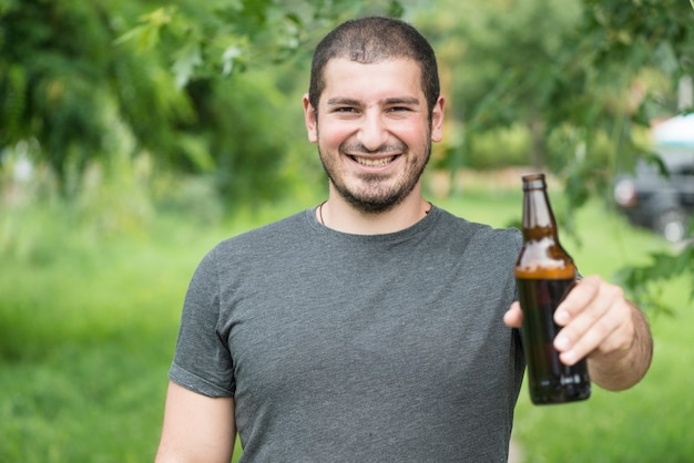 Homme gai acclamant avec bouteille à caméra
