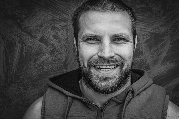 Homme gai adulte avec une barbe souriant gaiement.
