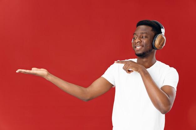 Homme gai d'apparence africaine dans des écouteurs faisant des gestes avec le fond d'isolement de mains