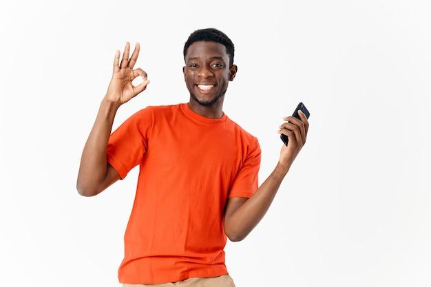Homme gai d'apparence africaine avec un téléphone entre les mains de la communication technologique
