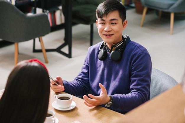 Homme gai assis avec un smartphone à la main et une tasse de café sur la table devant lui et souriant tout en parlant