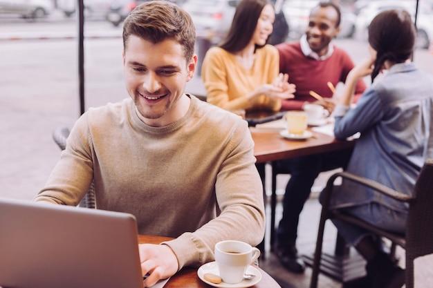 Homme gai attrayant assis au café tout en regardant l'écran et souriant