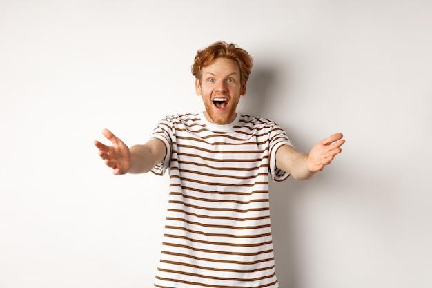 Un homme gai aux cheveux roux et bouclés, tendant les mains vers l'avant, étendant les bras pour vous accueillir ou vous féliciter, souriant heureux, debout sur fond blanc
