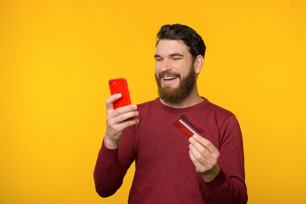 Homme gai barbu fait des achats en ligne à partir de smartphone.