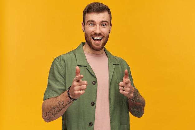 Homme gai, beau mec aux cheveux bruns et à la barbe. vêtu d'une veste verte à manches courtes. a un tatouage. vous pointer du doigt. isolé sur mur jaune