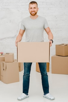 Homme gai avec boîte de carton