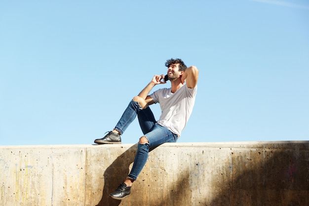 Homme gai complet du corps assis sur un mur de béton parler sur un téléphone intelligent