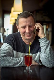 Homme gai dans un chandail parler sur un téléphone mobile dans un café confortable et rire. conversation agréable autour d'une tasse de thé. concept de technologies modernes et de communication mobile