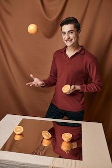 Homme gai dans une chemise rouge avec des oranges dans ses mains un miroir sur la table. photo de haute qualité