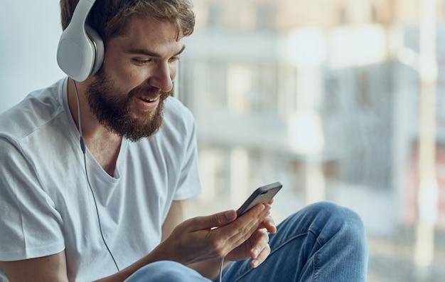 Homme gai dans les écouteurs écoute de la musique sur le rebord de la fenêtre