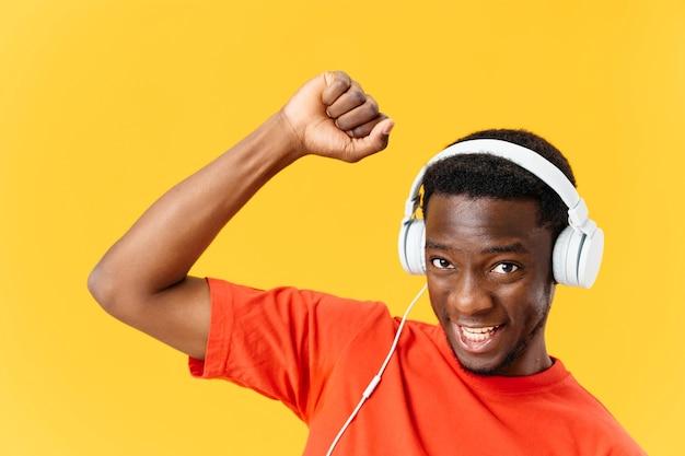 Homme gai dans les écouteurs et gesticulant avec ses mains musique de danse fond jaune
