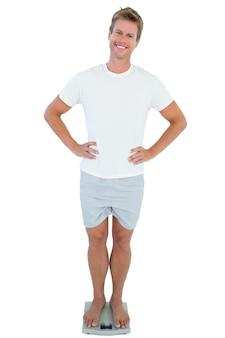 Homme gai debout sur une balance
