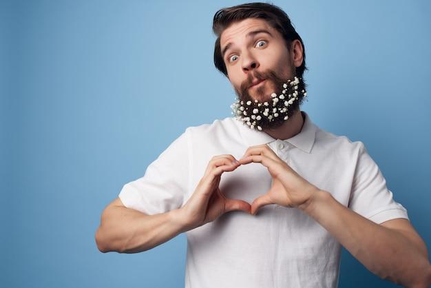 Homme gai avec des fleurs dans une chemise blanche de soin de cheveux de barbe fond bleu