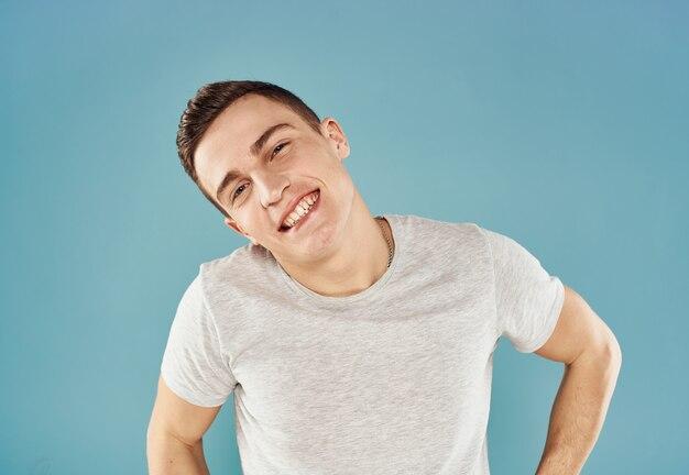 Homme gai en gestes d'émotions t-shirt blanc avec fond bleu mains. photo de haute qualité