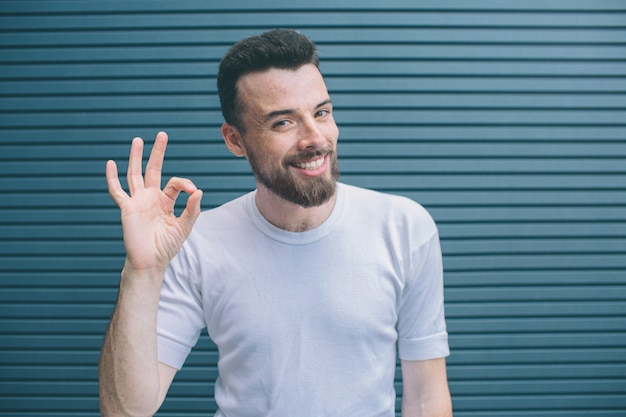 Un homme gai et heureux montre le symbole ok avec les doigts. il regarde la caméra et sourit. isolé sur rayé