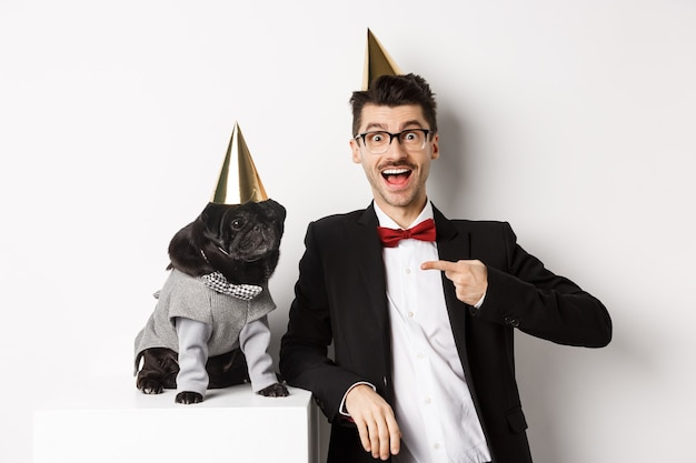 Homme gai et mignon carlin noir portant des cônes et des costumes de fête, propriétaire de chien célébrant l'anniversaire de son animal de compagnie, debout sur fond blanc.