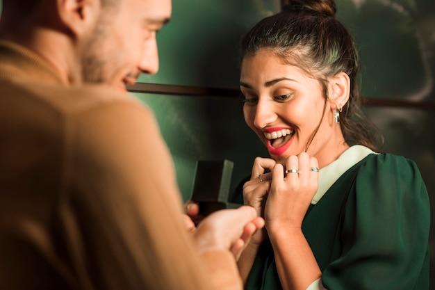 Homme gai présentant un cadeau dans une boîte à une jeune femme surprise