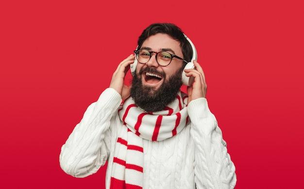 Homme gai en pull d'hiver et écharpe appréciant la musique avec des écouteurs