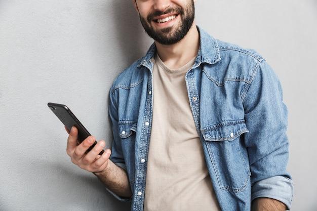 Homme gai recadrée portant une chemise isolée sur un mur gris, à l'aide de téléphone mobile