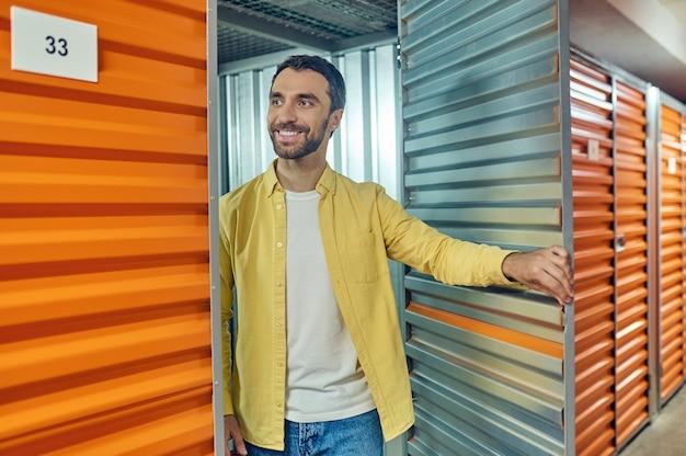 Homme gai se tenant près de la porte de garage