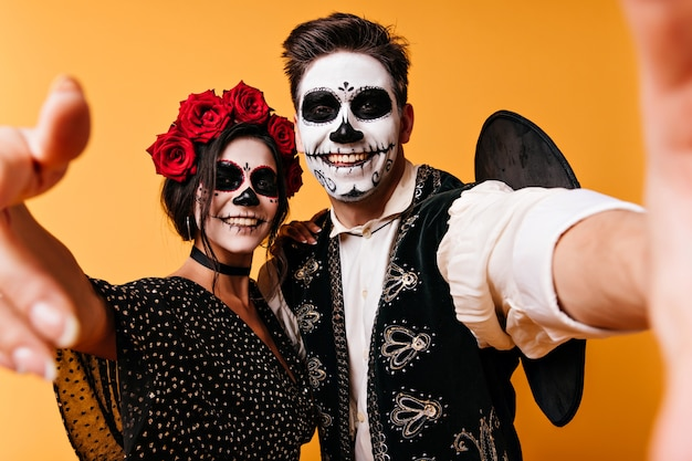 Homme gai en sombrero faisant selfie avec petite amie à halloween. des mecs drôles avec du maquillage de zombie refroidissant sur un mur orange