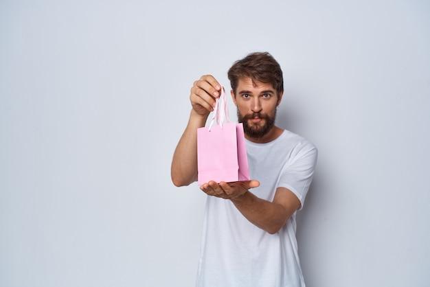 Homme gai en t-shirt blanc avec fond clair cadeau petit paquet rose