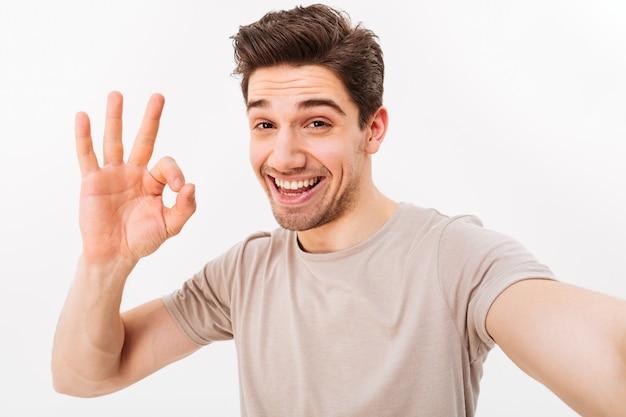 Homme gai en t-shirt décontracté et poils sur le visage souriant à la caméra avec un signe correct tout en prenant selfie, isolé sur mur blanc