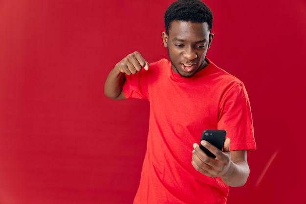 Homme gai téléphone d'apparence africaine dans les mains technologie fond isolé