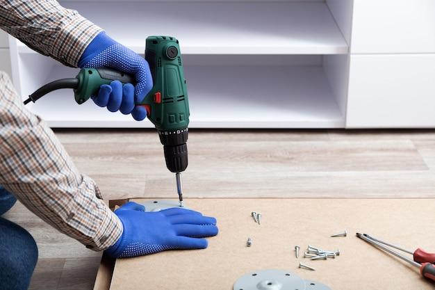 L'homme en gants assemble des meubles de table avec une perceuse. assemblage, maître de maison de réparation de meubles. main masculine avec perceuse au sol. espace de copie.
