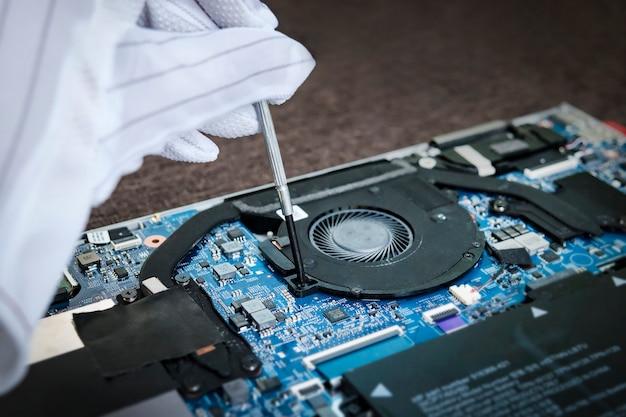 Homme en gants blancs installation d'un ventilateur d'ordinateur portable à l'aide d'un tournevis. refroidisseur de remplacement dans l'ultrabook mince moderne. rénovation propre.