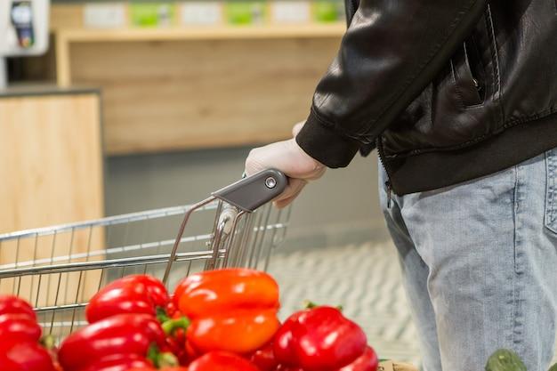 Homme en gants de latex blanc choisissant le poivron rouge dans la boutique. précautions pendant la quarantaine