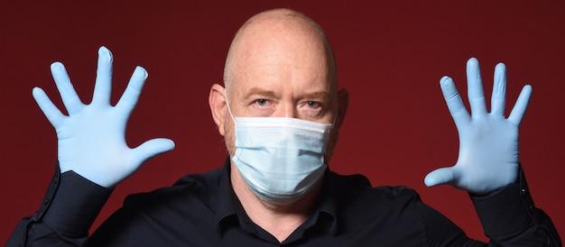 Homme avec gants et masque à mains ouvertes sur fond rouge