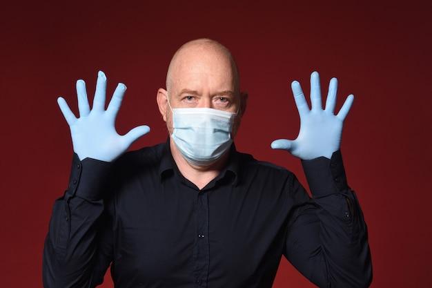 Homme avec des gants et un masque avec les mains ouvertes sur fond rouge