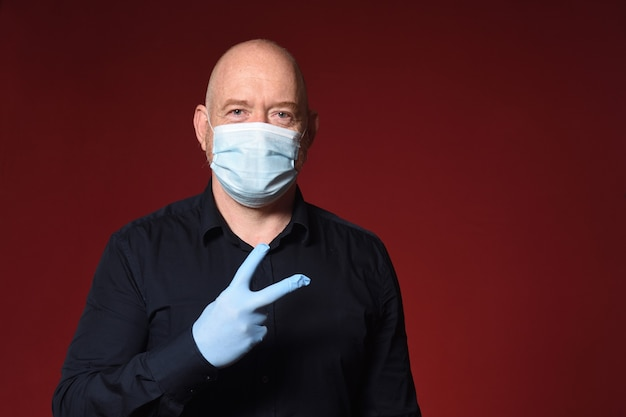 Homme avec gants et masque avec signe de la victoire sur fond rouge