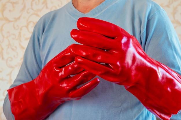 Homme en gants de protection en caoutchouc rouge