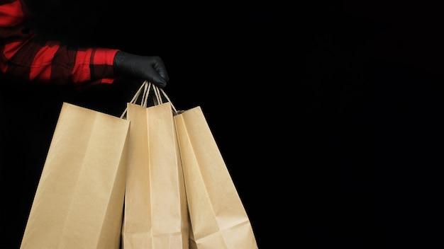 Un homme en gants de protection noirs tient un sac en papier avec des achats au magasin pendant les vacances du vendredi noir. le concept de vente et de shopping
