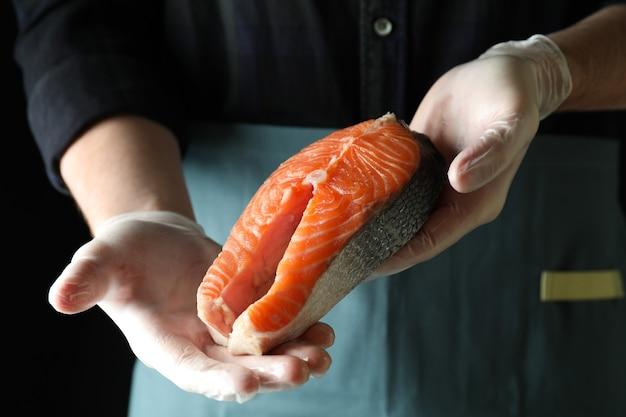 L'homme en gants tient la viande de saumon sur fond sombre