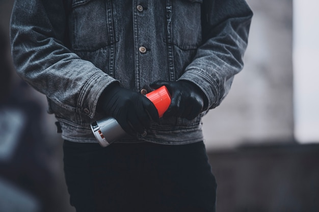 L'homme en gants et veste en jean prend une peinture en aérosol. jours gris du travail de graffeur