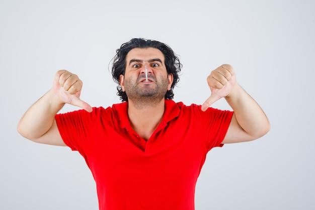 Homme gardant la cigarette dans la bouche, montrant le double pouce vers le bas en t-shirt rouge et l'air furieux.