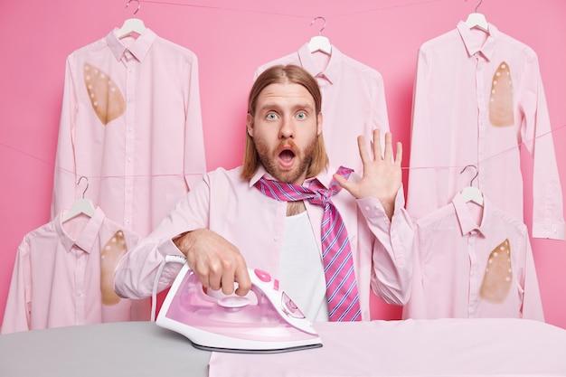 L'homme garde la bouche grande ouverte porte une chemise avec des fers à cravate se tient près d'une planche à repasser ne peut pas croire aux nouvelles choquantes d'être une femme de ménage occupée