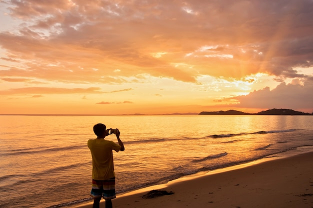 Un homme garde des souvenirs avec un téléphone appareil photo dans sa main