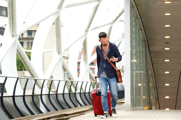 Homme à la gare avec valise et téléphone portable