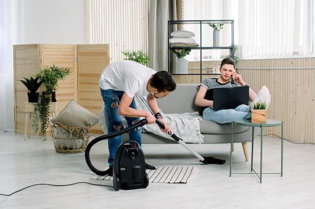 Homme gay nettoyant la maison aidant son mari pendant qu'il travaille sur un ordinateur portable.