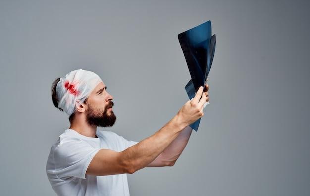 Un homme avec une gaze modèle de chirurgie de réanimation sanguine tête bandée sur son bras.