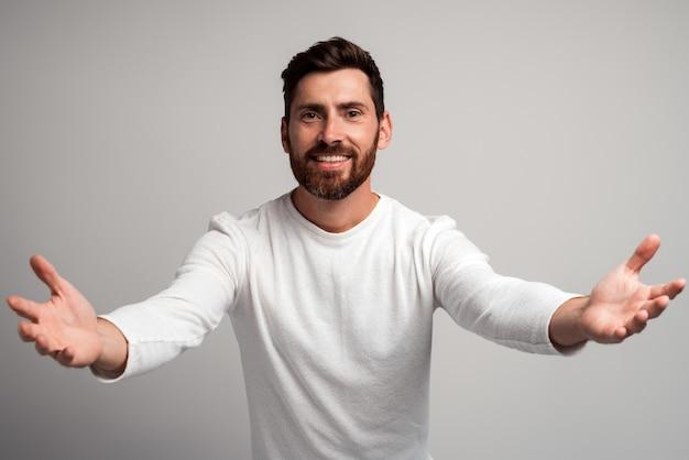 Homme généreux au cœur ouvert avec barbe partageant les mains ouvrantes regardant la caméra avec un sourire aimable, saluant et régalant, heureux heureux de vous voir. studio intérieur tourné isolé sur fond blanc